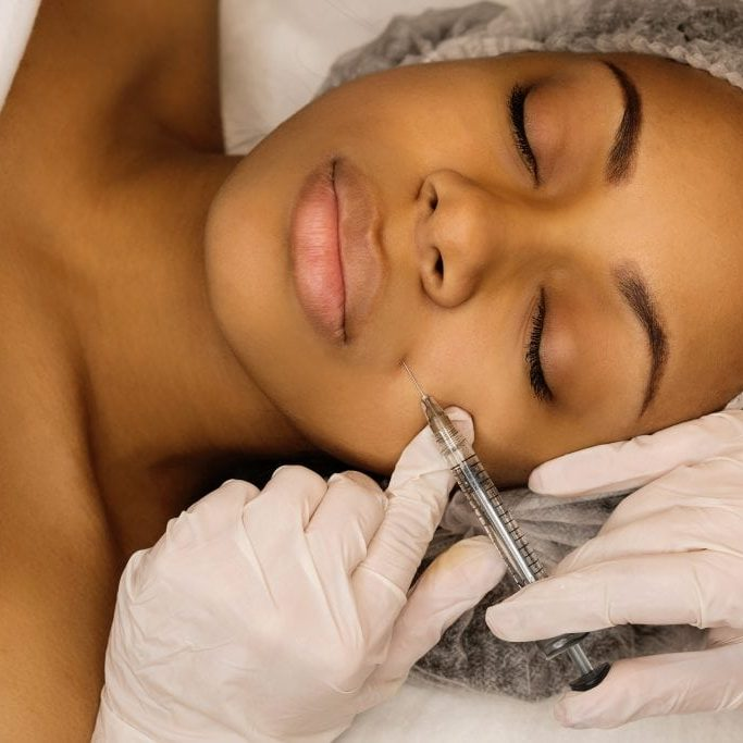 Injection cosmetology: contour plastic. Doctor makes rejuvenating facial injections procedure. Filling nasolabial fold with preparation with hyaluronic acid. Afro american woman receiving treatments